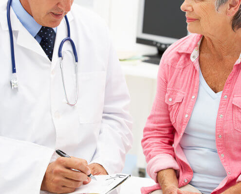 Doctor with female patient taking notes