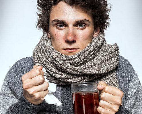 Man Cold / Ill young man with red nose, scarf, sneezing into handkerchief. Medication or drugs abuse, healthcare concept