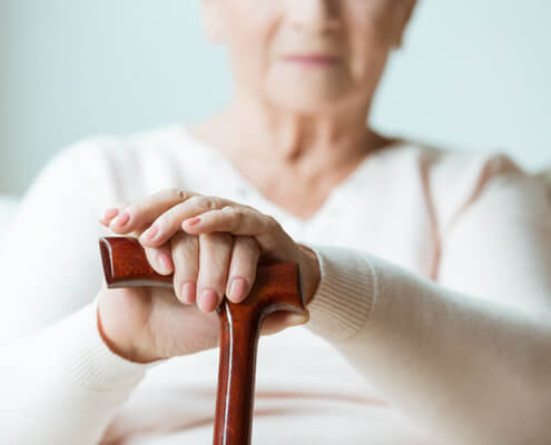 Elder holds hands on walking stick while sitting on white sofa in nursing home